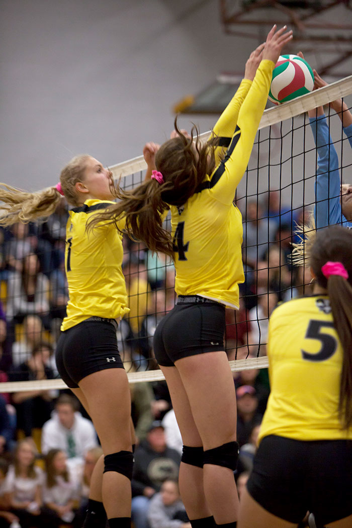Rattlers women's volleyball players go up for a block at the net.